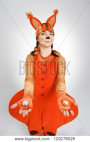 Young woman in the image of red squirrel with cookies