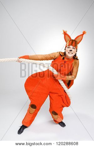 Young woman in image of red squirrel pulling a rope