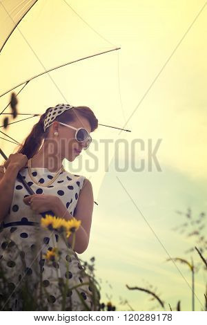 Young Woman With A Rockabilly Outfit And A Sunshade In A Meadow