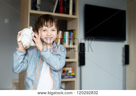 Little Boy Checking Content Of In His Piggy Bank