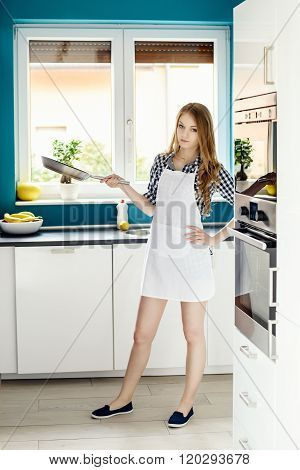 Young Beautiful Woman Posing In The Kitchen With A Frying Pan