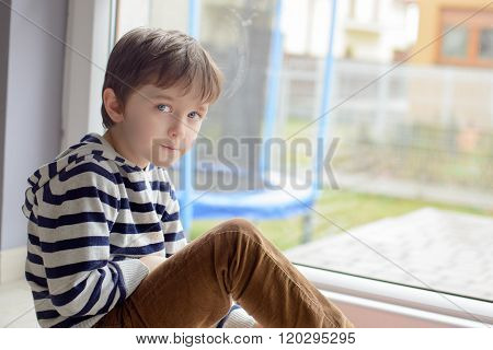 Little Boy Sitting Sitting On The Floor In Front Of A Window