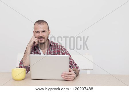 Young modern guy in office looking at camera.