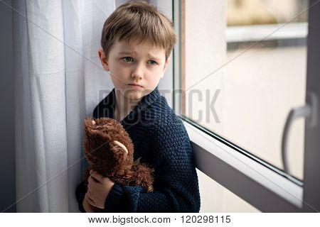 Boy Is Hugging His Teddy Bear. Standing By The Window.