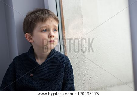 Sad 7 Years Boy Child Looking Out The Window.