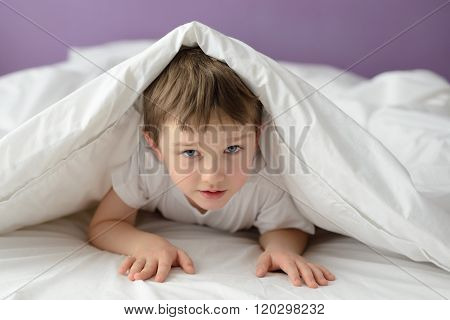7 Years Old Boy Hiding In Bed Under A White Blanket Or Coverlet