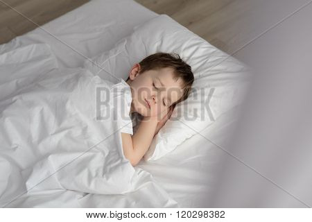Adorable Boy Sleeping In Bed, Happy Bedtime In White Bedroom