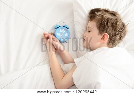 Top View Of Little Boy Sleeping In White Bed With Alarm Clock Near His Head.