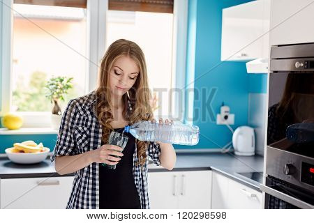 Beautiful Blonde Woman Pouring Water From A Bottle Into A Glass.