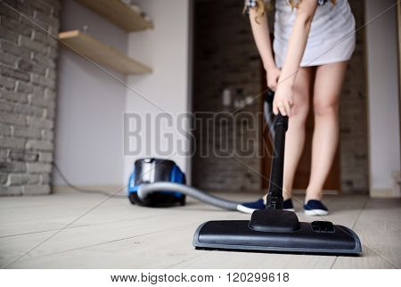 Woman Vacuuming The Floor.