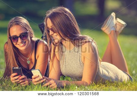 Two Young Girls Smiling And Using Your Smartphones