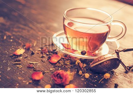 Glass tea cup with dry rosebuds
