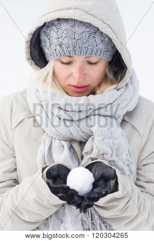 Girl  holding snowball in cold winter time.