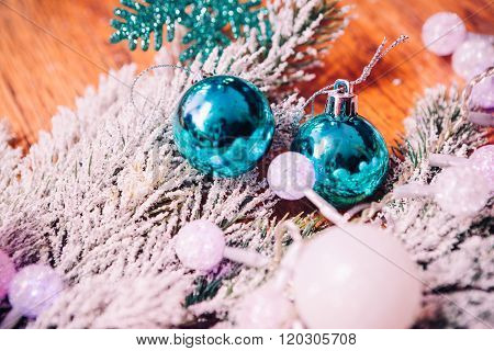 Spruce branches in the snow and blue balls wooden background