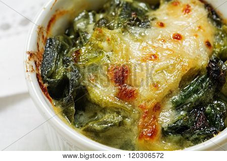 Closeup Of Baked Spinach With Cheese Crust In A Small Casserole On A White Napkin