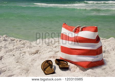 A beach bag and sandals on the sand near the ocean
