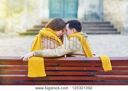 Two lovers sitting on bench in park and holding themselves by hands