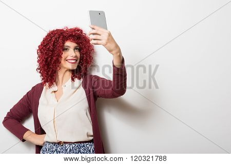 Curly redhead businesswoman taking a selfie on smartphone