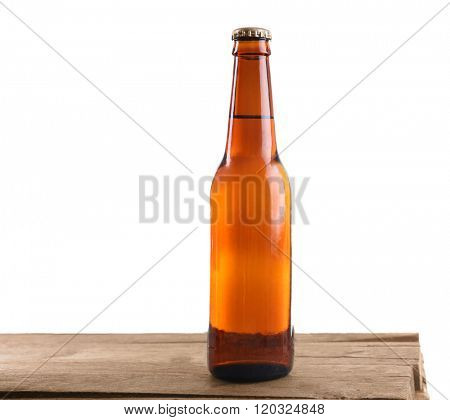 Unlabeled beer bottle on wooden table against white background