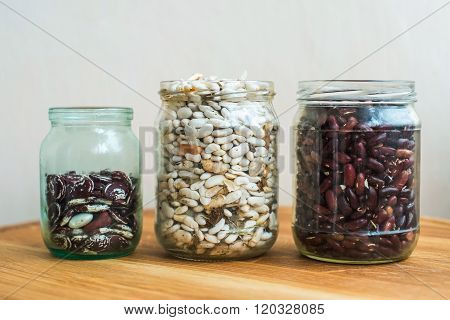 Three kind of sorts of beans in glass jars