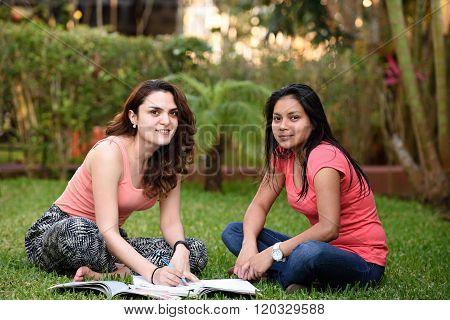 Two Girls Studying Sit Grass