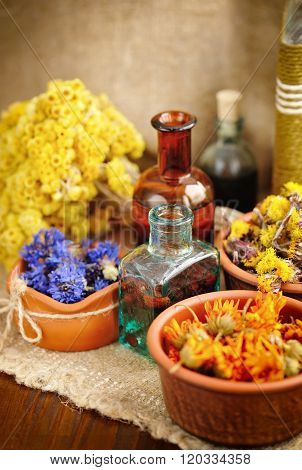 Healing Herbs And Tinctures In Bottles On Sackcloth, Dried Flowe