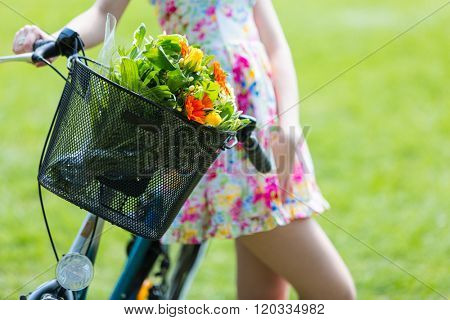 Young girl wearing a summer dress with a bouquet of flowers. With bike in park