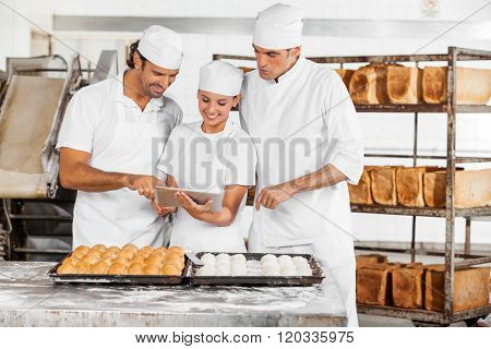 Baker's Using Tablet Computer Together In Bakery