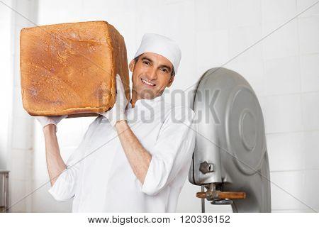 Confident Baker Carrying Big Bread Loaf On Shoulder In Bakery