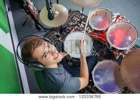 Confident Male Drummer Wearing Headphones While Performing