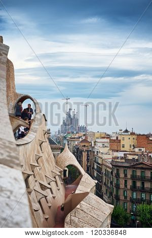 BARCELONA, SPAIN - CIRCA MAY 2015: Antoni Gaudi Architecture - View of Sagrada Familia Church in Distance Under Storm Clouds as seen from Rooftop of Casa Mila in Barcelona, Spain