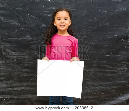 little cute girl holding an empty paper sheet with blackboard on the background
