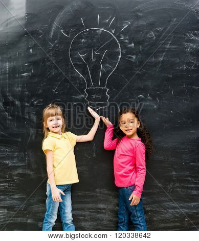 two cute little girls showing drawn lamp on the blackboard with hands