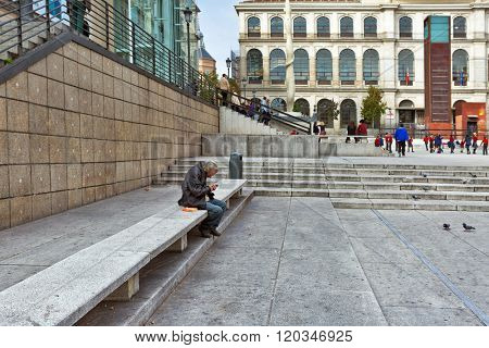 MADRID, SPAIN - OCTOBER 26, 2015 : tired man resting on a bench in front of the Reina Sofia Museum, dedicated to the exhibition of modern and contemporary art