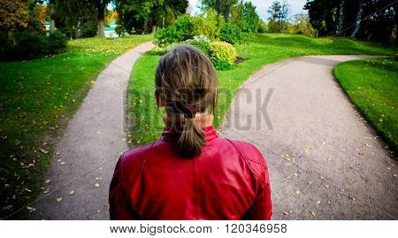 Girl in red jacket standing on the fork of two roads.