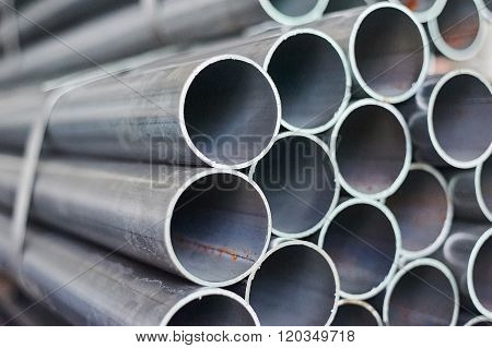 Metal Pipes In A Warehouse. Stacks Of New Round Steel Pipe In Factory