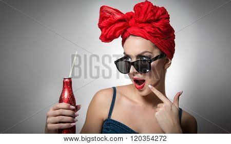 Woman with red turban and sunglasses holding a drink bottle with a straw inside. Attractive girl