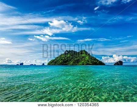 Vacation holidays concept background - tropical island and long-tail boat in sea. Thailand