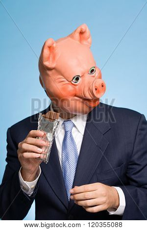 Man in a pig mask eating chocolate