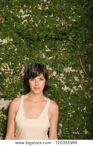 Woman in front of wall of leaves