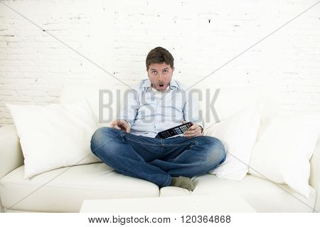 young man watching tv sitting at home living room sofa holding remote control looking intense and very interested enjoying television program or movie in disbelief amazed and shock face expression