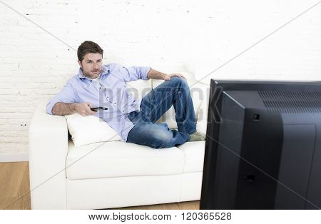 young happy man watching tv lying at home living room sofa with remote control looking relaxed enjoying television program or movie