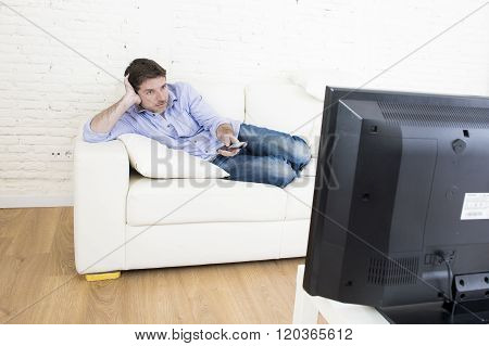 young happy man watching tv lying at home living room sofa with remote control looking intense and very interested enjoying television program or movie