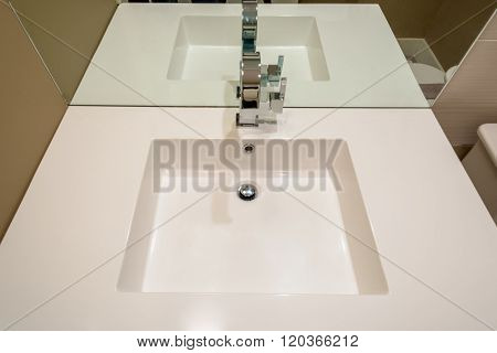 Clean bright white bathroom sink with faucet.
