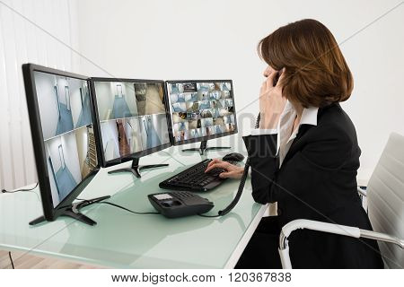 Female Operator Looking At Multiple Camera Footage On Computers