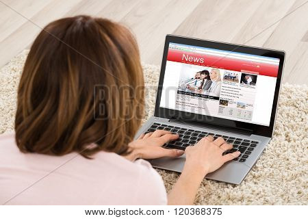 Woman Watching Online News Site On Laptop