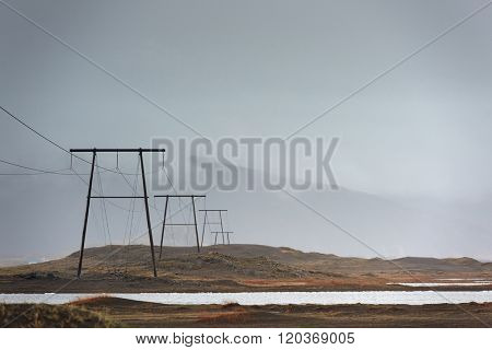 High voltage power lines electric pylons over land, in misty cloudy stormy landscape with mountains in the background