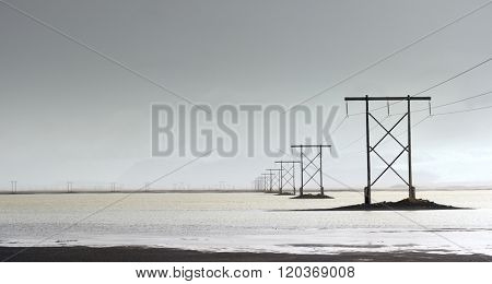 Panorama of high voltage power lines electric pylons over water, in misty cloudy stormy landscape