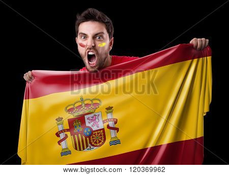Fan holding the flag of Spain on black background