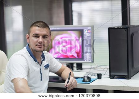 creative worker, photo editor working on graphic tablet at his desktop computer at small startup office